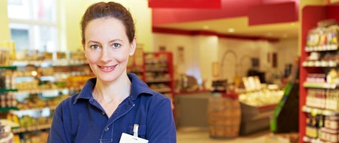 Lächelnde ältere Marktleiterin im Supermarkt mit verschränkten Armen